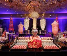 A wondrous wedding candy station holds seventy five containers of various sweet treats in shades of pink, white and silver.
