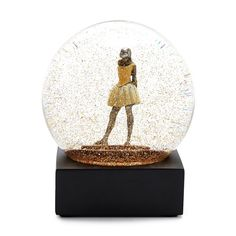 """A tiny reproduction of Degas' """"Little Dancer of Fourteen Years"""" stands center stage amid the swirling, fluid world of this snow globe. The golden confetti appears to celebrate her extraordinary performance. Each globe melds sophistication with whimsical delight."""