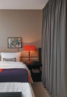 O abajur laranja da Marché Art de Vie quebra a formalidade do espaço criado pela decoradora Adriana Penteado, onde predominam tons de bege e cinza. A mesma cor vibrante aparece em detalhes da manta (Empório Beraldin). Roupa de cama do Mundo do Enxoval e cabeceira da Brentwood.