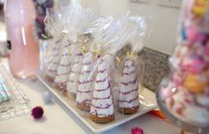 Unicorn horn treats as a party favor - ice cream cones dipped in white chocolate with a spiral, wrapped in cellophane and gold ribbon