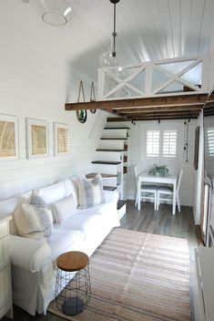 Coastal living room with white couch and rustic beams
