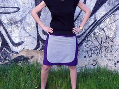Falda morada (tela villela), cintura elástica negra. Bolsillo grande central.