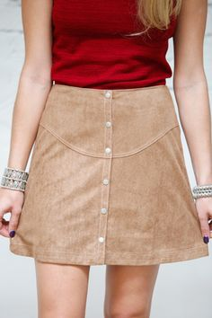 The Crosby Mini Skirt features a button up front, suede fabric, and dark camel color with a high waist fit. Pair it with a tight mock neck tank or bodysuit for the ultimate holiday party look.