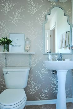 Update a boring, builder powder room with a few simple changes. Hang temporary wallpaper on one wall, add a mirror (spray-painted to match), a simple shelf and some decorative accessories. Big impact for a small budget.