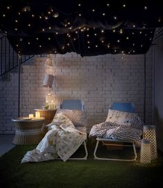 Two outdoor chaises with blankets and pillows are surrounded by candles, under a starry night sky.