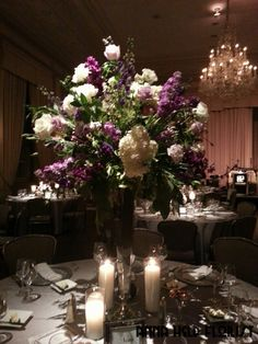 Traditional elevated wedding centerpiece with white hydrangeas, purple stock, lavender larkspur, purple dendrobium orchids on polished silver risers. Styled by Anna Held Florist, Chicago.