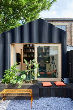 To build this modern backyard studio, a modular timber frame system was constructed using full sheets of plywood, and black lightweight corrugated fibreglass panels were used on the exterior. #BackyardStudio #BackyardOffice #GardenStudio