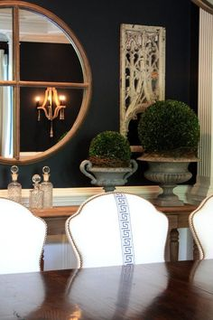 Formal dining room with dark walls, architectural salvaged window frames with scrollwork, oversized zinc urns with greenery, white upholstered chairs with a simple blue patterned Roman key design.  Black, blue, gold, white, green
