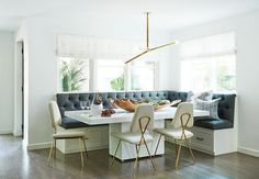 Under windows dressed in white roman shades, an l-shaped white dining banquette fitted with drawers and charcoal gray tufted cushions sits facing a modern glossy white dining table seating Jonathan Adler Maxime Dining  Chairs lit by a modern brass chandelier.
