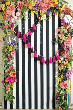 ビビッドでカラフルな花でアーチ状に囲い、タッセルやガーランド、フォトプロップスを飾ることでPOPな雰囲気が楽しいフォトブース。
