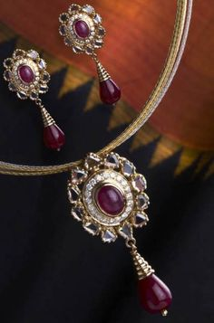Classic diamond and ruby set of pendant and earrings is handcrafted in 18k gold.