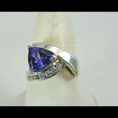 14K WG Tanzanite Trillion & Diamond Ring Size 7.5. trillion cut Tanzanite which measures approx. 8mm along each edge. Ring is accented with 6 small clear round stones along one edge that appear to be diamonds with an approx. 1.5mm each. 14K WG, actually yellow gold with a white gold rhodium plating which is showing a little wear, ring is inused condition. Jewelry Rings