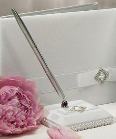 Pure Elegance Wedding Pen Set features a base covered in white satin. It is then decorated with a band of white satin layered with a white satin bow. The bow is decorated with a diamond shaped crystal brooch.