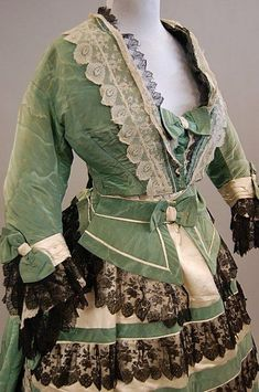 A green watered silk formal gown, circa 1865, the Sign In to see what this sold for A green watered silk formal gown, circa 1865, the lightly padded bodice trimmed with cream and black lace and bows, the horizontally banded skirt with matching waist-sash, (3)