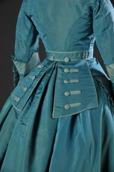 Back view, Dress in turquoise and light blue silk taffeta, 1865-69. This dress in turquoise and pale blue taffeta silk has a train and a separate waistband with panels at the back, with large decorative buttons. The daytime corsage has a V-shaped neckline and pagoda sleeves. It was worn over a chemisette. The dress is decorated with ribbons, bows, flouncing and bands of densely gathered fabric. Source: MODEMUSEUM HASSELT