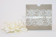 Handmade wedding invitation - A vintage chic look with earthy kraft paper square pouch, decorated with ivory lace, ivory satin ribbon and embellished with a pearl button. Invitation inside the pouch is printed on ivory metallic card.