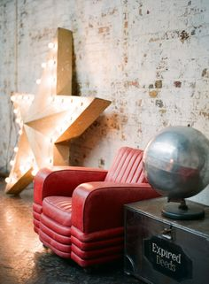 This is drool-worthy. Art deco red leather chair, steel 'globe', Marquee Star, and steel steamer trunk.