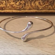 Tiffany & Co. Teardrop Bangle AUTHENTIC! Just in from getting cleaned at the Tiffany & Co. store! Comes with pouch, box, and cleaning clothing. I've had this bracelet for 11 years. Micro scratches (as described by my guy at Tiffany's) shown in the photos. No trades. No bundling with this items. Bundled orders will be cancelled. Don't be shy... Send me an offer! I will entertain ALL offers (accept or counter on initial offer).  Tiffany & Co. Jewelry Bracelets