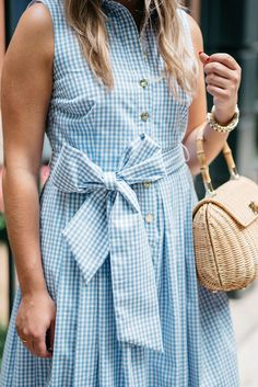 Blogger Jessica Sturdy of Bows & Sequins wearing a blue and white gingham dress with a big bow tie. Styled with a straw hat and wicker rattan tote for a summertime Saturday outfit!