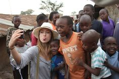 Olivia Wilde demonstrates to Kenyan children how to make faces for a photo, during the Half the Sky shoot.
