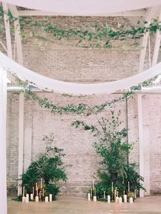 Incredible Wedding Decor Ideas for Your Ceremony Altar | Candles and greenery are simple wedding decorations that can make a huge statement. Choose greenery as the focal point of the altar and add gold candlesticks to contrast for a dreamy, earthy vibe.
