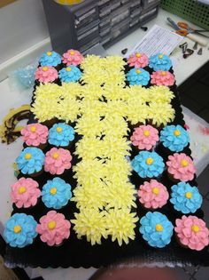 Cupcakes idea - the cross in yellow stands out from the pink and blue - These cupcakes are flower-topped with icing.