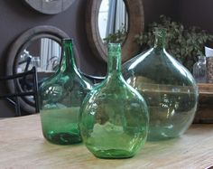 Big ol' glass bottles... I finally found out what they are called: A demijohn