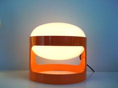 KD 27 (1967) di Joe Colombo. La base, un cilindro svuotato in resina ABS, sostiene una doppia calotta circolare che ha la funzione di schermare la lampadina a incandescenza. Una lampada da tavolo entrata nella storia del design italiano e della produzione Kartell.