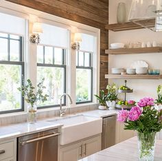 white kitchen with farmhouse sink and wood accent wall