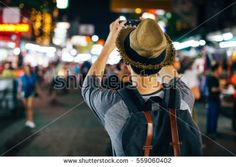 Young Asian traveler taking photo with mobile phone in Khaosan road at night in Bangkok, Thailand