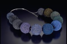 Necklace |  Amy Karesh.  Beadwoven spheres are executed in peyote stitch over a hardwood sphere