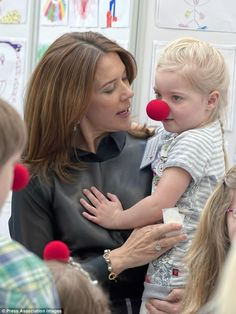 A royal touch: The Australian-born Danish royal held and cuddled the children...