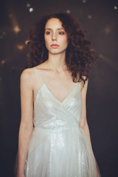 This beauty is plentifully bestrewn with silver sequins and lightly covered with a hand-pleated soft tulle overlay for the perfect amount of sparkle. It has a silk charmeuse slip and lining, and is cut on the bias to show off your curves while maintaing a flouncy skirt. Any woman would feel starry-e