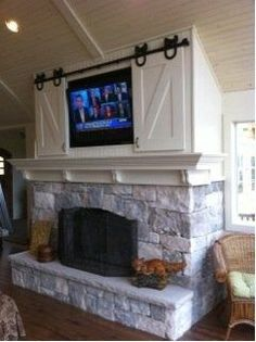 river rock fireplace with barn door and cabinets | sliding barn doors to hide t.v..