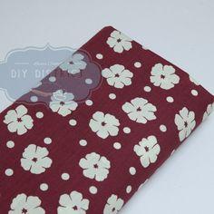 Tissu fleurs blanches fond bordeaux.