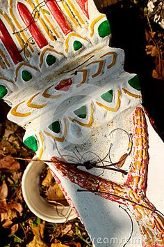 View of colorful painted Pedestal base used to support local spirit houses in Southeast Asia, lying in a field under shadows among dry leaves near a holy meditation site. It is painted with gold, green, yellow, and red accents.