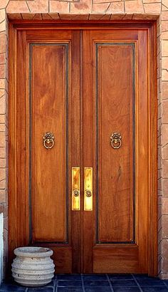 Honduras mahogany double doors with patina copper. I love the knockers and the symmetry of the door knobs.
