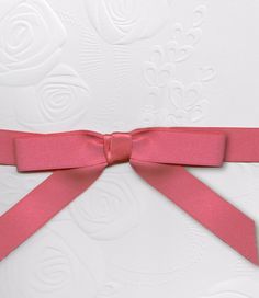 Our Embossed Rosette top-fold invitation is shown here in detail with a peony-hued ribbon.