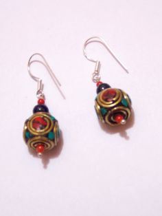 brass earrings with stone work on it. Silver wire for your ears. A pair of awesome earrings made of brass and stones. Rajasthani look.