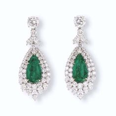 A PAIR OF EMERALD AND DIAMOND EAR PENDANTS, BY HARRY WINSTON    Each set with a pear-shaped emerald weighing 7.67 and 8.12 carats within a two-tiered brilliant, pear and marquise-cut diamond surround, suspended by a marquise and brilliant-cut diamond surmount to the brilliant-cut diamond top weighing 2.82 and 2.76 carats, mounted in platinum and 18k gold, 6.4 cm long    With maker's mark for Harry Winston, no. 6693