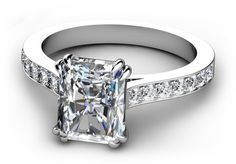 Double claw corner set rectangular radiant cut diamond engagement ring with bead set brilliant cut diamond upswept shoulders on a flat band.