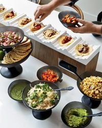 """Crown Moulding Taco Station  """"I love serving food in nooks and valleys,"""" says Girard. When Spiegel wanted to set up a taco bar, Girard realized that wavy crown molding from a lumber store would be perfect for holding the tortillas. She sets the toppings in resin bowls by Tina Frey."""