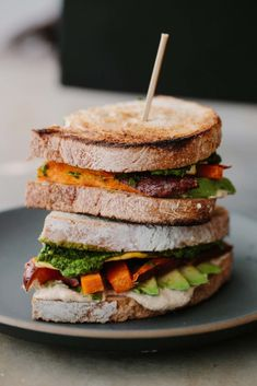 A hearty and veg-heavy fried egg sandwich made with roasted sweet potatoss, hummus, avocado, and a delightful kale-herb sauce.