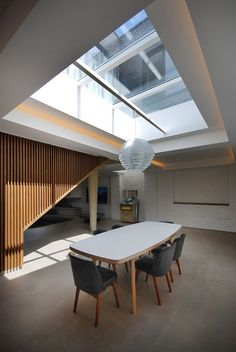 In the dining room, a James Burleigh table sits beneath a sizeable skylight. Throughout the ground floor, additional lighting is recessed in the coffered ceilings. Painted brick walls provide a reminder of the building's industrial past. Interior Architecture, Interior And Exterior, Interior Design, British Architecture, Modern Interior, Diy Design, Design Ideas, Fran Silvestre, Painted Brick Walls