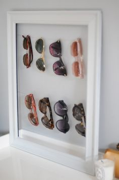 To organize sunglasses, attach picture hanging wire to a vintage frame. Then hang all your sunnies for a fun (and accessible) display!