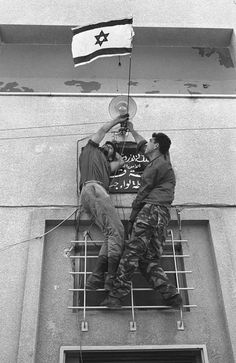 Israeli soldiers place a flag above the entrance to a Jordanian police headquarters after capturing it in the West Bank town of Jenin during the Six Day War June, 1967.