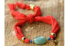 Rode Zijden Armband Groene Half-edelsteen Ster   Deze rode zijden armband is voorzien van een groene half-edelsteen, een goudkleurige ster, het Bazou embleem en kleine blauwe kraaltjes.   #bazou #bracelet #armband #silk #zijde #star #rendezvousofstyle