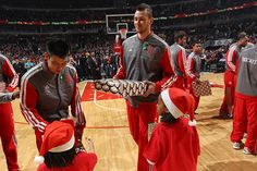 Jeremy Lin, left, and Donatas Motiejunas of the Houston Rockets present patients of the Ann & Robert H. Lurie Children's Hospital of Chicago with presents prior to the start of a Christmas Day game against the Chicago Bulls on December 25, 2012 at the United Center in Chicago, Illinois. (Photo by Gary Dineen/Getty Images)