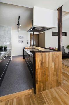 キッチン前壁にミャンマーチークを使用したヘリンボーン貼りが象徴的なリノベーション物件になります。 対面キッチンが開放感を持たせてくれる設計にしました。 キッチンのタイルがヘリンボーン貼りのスパイスになり、大人なヴィンテージ感をかもし出している。