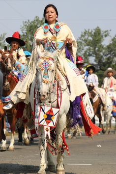 Woman riding in the horse parade at the Crow Fair in August 2013. Note the regalia on the horse's head.